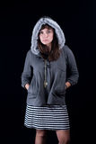 Young woman. A young woman on a plain black background wearing a gray fur lined hoodie and striped dress Stock Photography