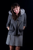 Young woman. A young woman on a plain black background wearing a gray fur lined hoodie and striped dress Royalty Free Stock Image