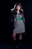 Young woman. A young woman on a plain black background wearing a striped dress Stock Images