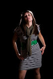 Young woman. A young woman on a plain black background wearing a striped dress Royalty Free Stock Photos