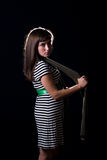 Young woman. A young woman on a plain black background wearing a striped dress Stock Photos