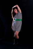 Young woman. A young woman on a plain black background wearing a striped dress Stock Photography