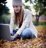 Young Woman. Young college woman works on her laptop in the middle of a park Stock Photo