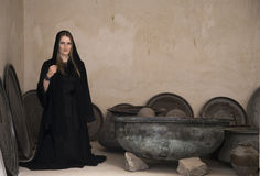Young woman in abaya in the middle of old cooking pots. Young woman in tradititional Emirati dress, called abaya in the middle of old cooking pots Royalty Free Stock Photos