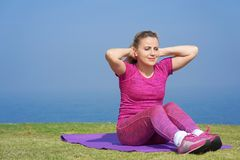 Girl doing exercises sitting on the background of the sea stock photography