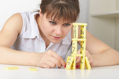 Young woman accurately builds tower of dominoes Stock Image