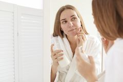 Young woman with acne problem holding bottle stock photography