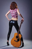 Young woman with an acoustic guitar on a black background, rear Royalty Free Stock Photography