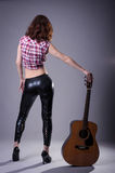 Young woman with an acoustic guitar on a black background, rear. View. A woman in leather pants and a shirt posing while standing, holding a guitar Royalty Free Stock Photos