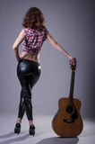 Young woman with an acoustic guitar on a black background, rear Stock Photography