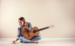 Young woman with acoustic guitar composing song near grey wall. Space for text royalty free stock image