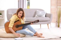 Young woman with acoustic guitar composing song. In living room. Space for text royalty free stock photo