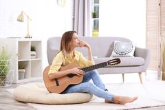 Young woman with acoustic guitar. In living room royalty free stock photos
