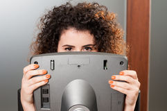 Young woman acting funny and hiding behind stepper monitor Stock Photography