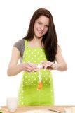 Young woman adding eggs to baking powder Stock Photo