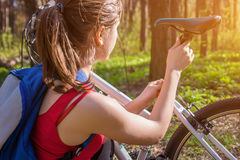 Young woman adjusting a saddle on her bicycle Royalty Free Stock Photos