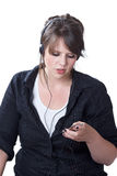 Young woman adjusts her portable music player. While wearing headphones; isolated on a white background Royalty Free Stock Images