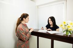 Young woman administrator in a dental clinic in the workplace. Admission of the client. Young women administrator in a dental clinic in the workplace. Admission royalty free stock images