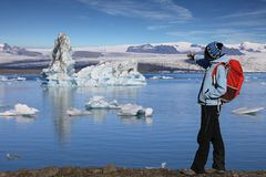 Young woman admires the beauty of the glacial lagoon Jokulsarlon Stock Photo