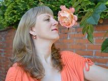 The young woman admires a tea rose Stock Photos