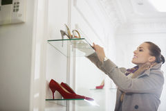Young woman admiring footwear in store Stock Image