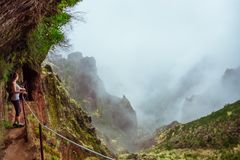 Young woman admiring the highland from one of the beautiful hiki. Ng trails of Madeira Island, Portugal Royalty Free Stock Photo