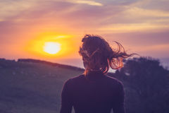 Young woman admiring the sunset over fields Royalty Free Stock Images