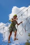 Young woman in adventure park summer challenge. Young woman in adventure park challenge concept Stock Photo