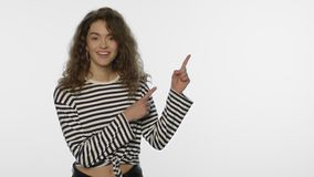 Young woman advertising product with hand gesture on white background. Portrait of surprised woman showing product in studio. Happy female person presenting stock footage