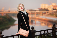 Young fashion woman with handbag outdoor. Young blond fashion woman with handbag against an autumn urban landscape Stock Images