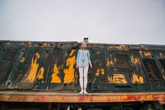 Young woman against the background of the thrown rusty railway car royalty free stock images