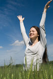 Young woman against the blue sky. Happy beautiful girl against the blue sky Royalty Free Stock Photo