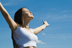 Young woman against the blue sky. Happy beautiful girl against the blue sky Royalty Free Stock Images