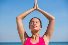 Young woman against blue sky exercising at beach. Young woman with eyes closed against blue sky exercising at beach Stock Photos