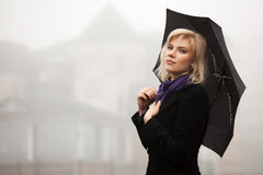 Sad young fashion woman with umbrella walking in a fog Stock Images