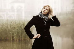 Young blond fashion woman in black coat walking outdoor Royalty Free Stock Photography