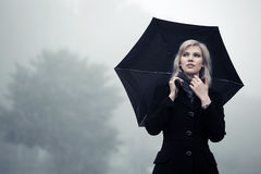 Young fashion woman in black classic coat with umbrella  Royalty Free Stock Images