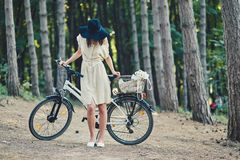Young woman against nature background with bike. Young hipster woman against nature background with bike Stock Photos