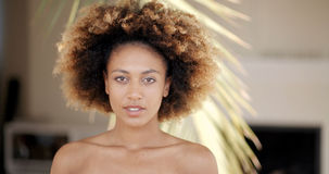 Young Woman Against Palm Tree Branch. Portrait of a young african american woman against palm tree branch Stock Photo