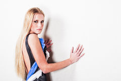 Young woman against wall. A young woman leaning against a white wall Stock Photography