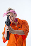 Young woman aiming with automatic rifle. Dangerous young woman in orange shirt holding automatic rifle Royalty Free Stock Images