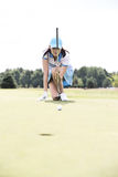 Young woman aiming ball while kneeling at golf course Royalty Free Stock Photo