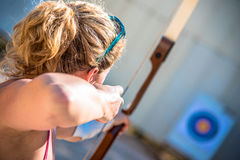 Young woman aiming with a bow. To a target Stock Photos