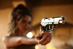 Young woman aiming gun Royalty Free Stock Images