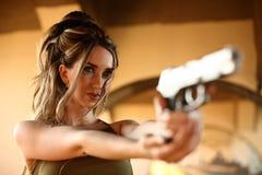 Young woman aiming gun Royalty Free Stock Photos