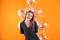 Young woman with air balloons. On color background royalty free stock photo