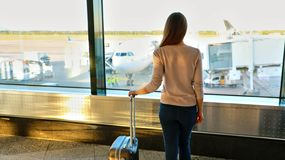 Young woman in the airport looking through the window at airplanes stock photos