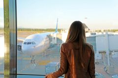 Young woman in the airport looking through the window at airplanes stock images