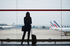 Young woman in the airport, looking through the window at planes Royalty Free Stock Photography