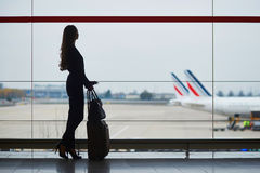 Young woman in the airport, looking through the window at planes Stock Photos
